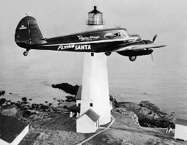 Flying Santa plane in front of lighthouse